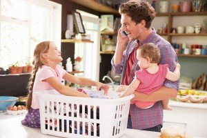 Availability Father Using Mobile Phone As He Sorts Laundry With Children sell my College Station house fast