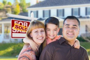 Sell my house fast Houston | Young Family in Front of Sold Real Estate Sign House