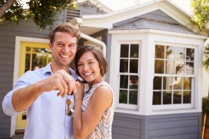 Punctuality Couple with keys standing outside new home sell my Houston house fast