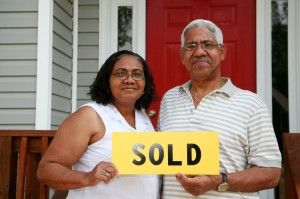Older couple holding a sold sign saying Sell My House Quickly Katy