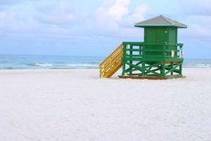 A green lifeguard hut on an empty morning beach